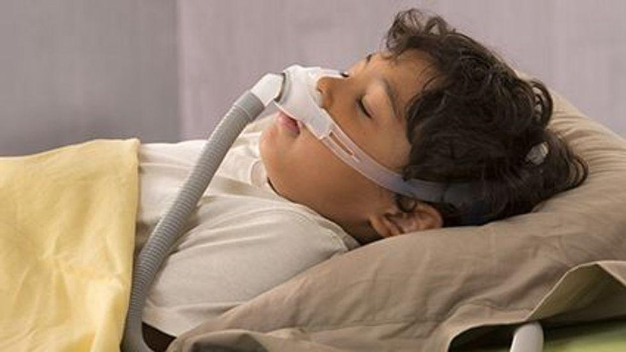 a child asleep with a breathing mask on