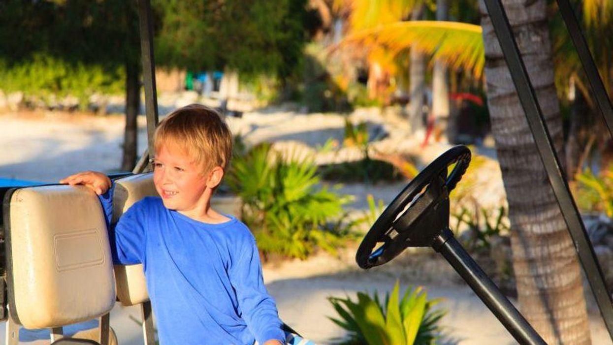 boy driving golf cart