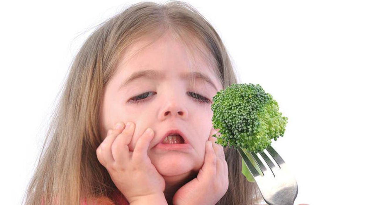 unhappy girl that doesn't want to eat broccoli
