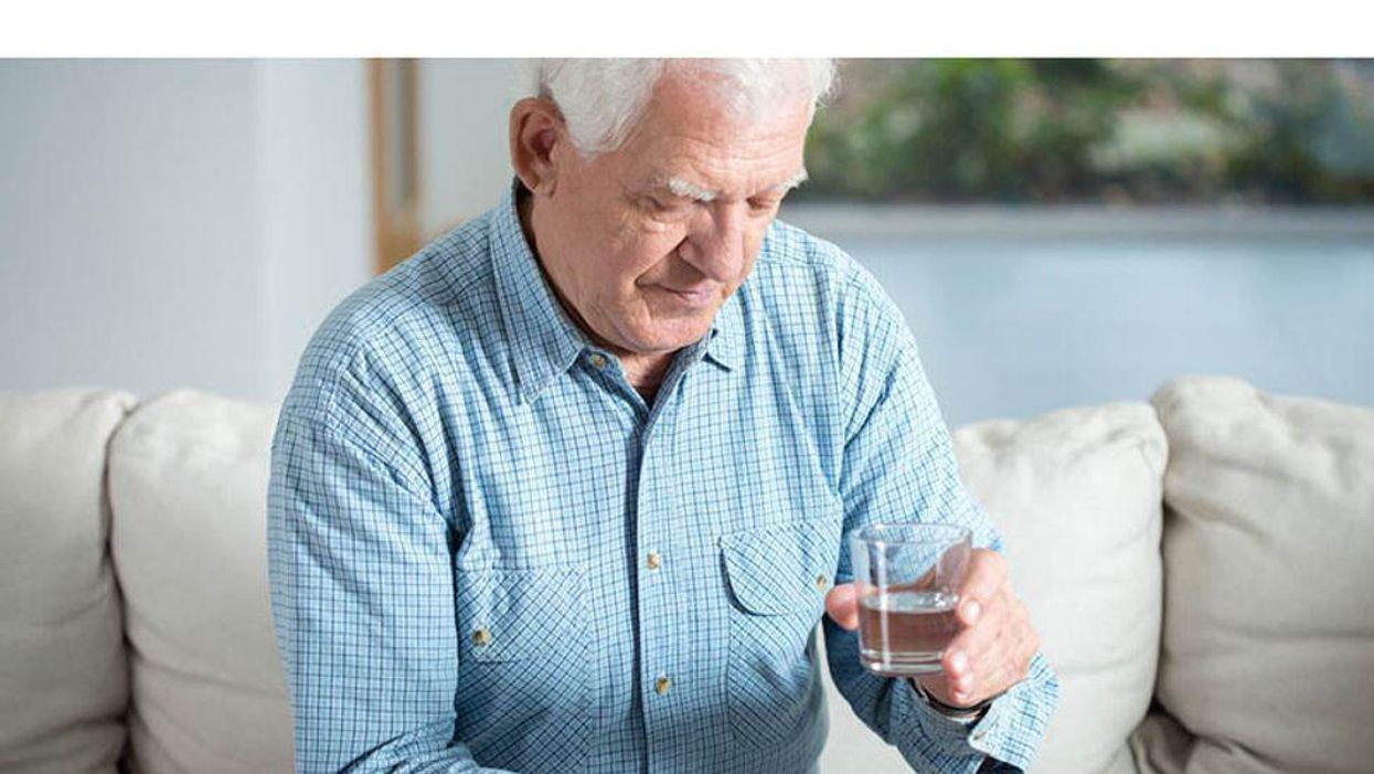 man sitting on the couch ready to swallow his pills