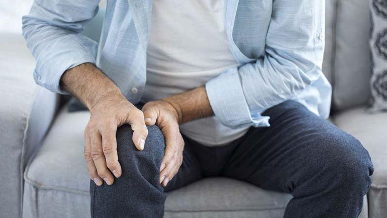 man holding his knee in pain sitting on the chair