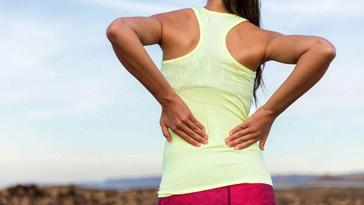 girl holding her back in pain